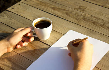 Male hands holding a cup of coffee.