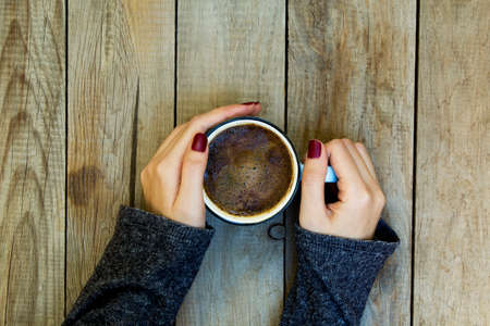 Woman hand holding coffee cup on wooden table.