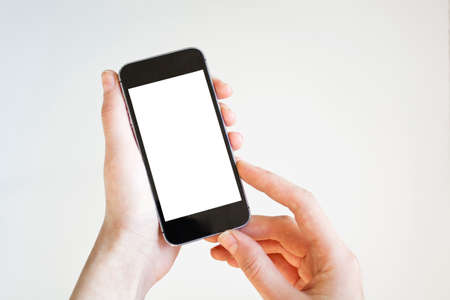 Woman hand holding blank smartphone with blank screen isolated on white background.