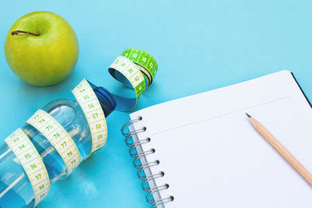 Fresh apple, measuring tape, water bottle and notebook on blue background. Stock Photo