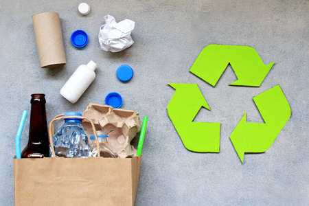 Recycling symbol and different garbage on gray background. Top view.