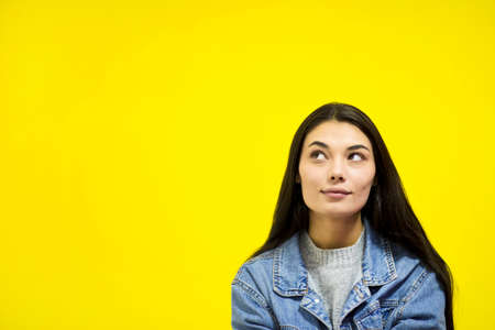 Young beautiful woman looking away at copy space isolated on yellow background.