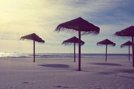 color tone: Wooden sun umbrellas silhouettes on the sea beach. Vacation concept in vintage color tone. Costa Dorada, Spain.