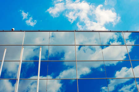 building wall: Glass wall of the modern business office building. Abstract architectural blue background. Window reflection.