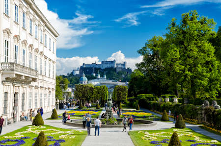 flowerbeds: Salzburg, Austria - May 7, 2016: Beautiful view of Mirabell Gadens in Salzburg. Spring blooming flowerbeds, green trees, people walking through the alleys. Fortress Hohensalzburg in the background.