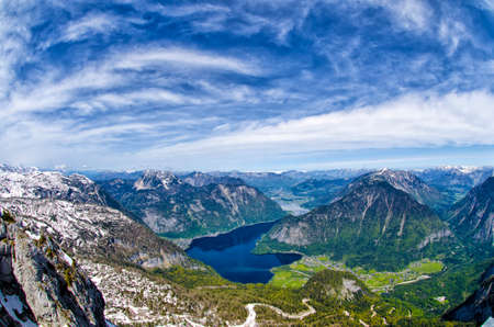 Panoramic aerial view of Alps mountains, snowy mountains peaks and Hallstattersee lake. Fisheye lens view. Austrian Alpine landscape in springtime. Salzkammergut, Austria. Stock Photo
