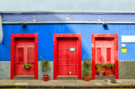 cristobal: Blue house with three red doors in the old Town of San Cristobal de La Laguna. Architectural detail of creative colorful house. Color blocks architecture background. Tenerife, Canary Islands Stock Photo