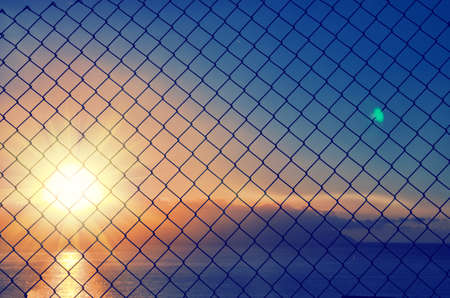 Close up of mesh fence against the blurred sunset sky. Abstract blue orange background.
