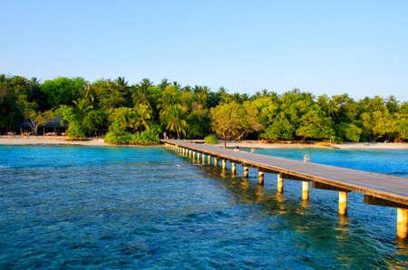 Long wooden pier or bridge to the island with tropical garden. 版權商用圖片