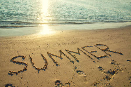 Word summer written on white sand beach. Summer holiday, travel and vacation concept. 版權商用圖片