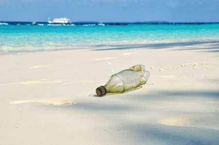 Plastic single-use bottle on beautiful white sand tropical beach.