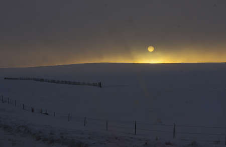 prairie winter sunset with moon and snow photo