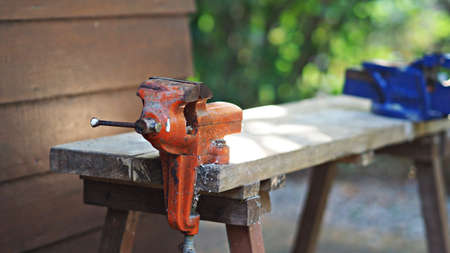Orange rustic vice clamp sitting on workbench in garden.