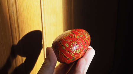 Colorful Easter egg in woman hand with light and shadow.