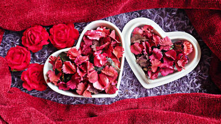 Heart-shaped ceramic cup with dry flowers and leaves on fluffy purple rug.  Valentines day and anniversary background.