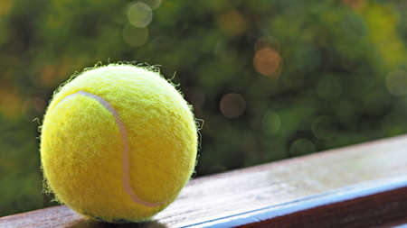 Close up tennis ball on wooden floor with green background. Tennis sports background.
