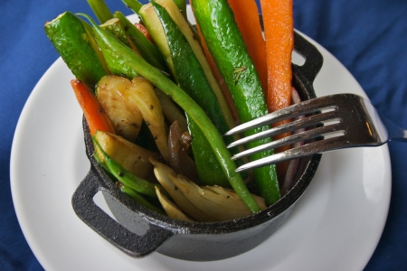 Julienned vegetables in small iron pot on white plate