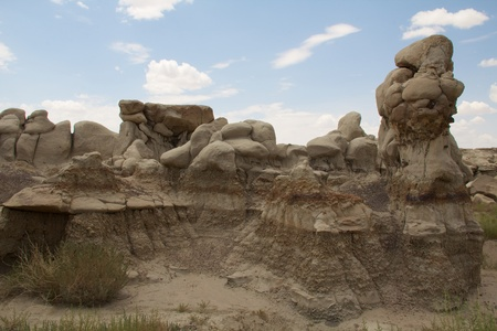 hoodoos: Chain of gray hoodoos against blue sky and scattered clouds at Bisti badlands Stock Photo