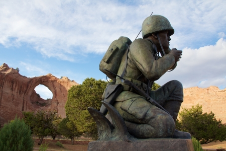 Window Rock near sunset, with kneeling Navajo code talker statue in foreground, horizontal Sajtókép