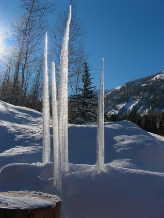 shadowed: Four icicles in shadowed snow against blue sky and mountains