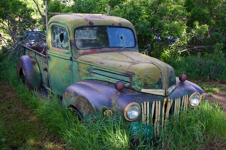 Multicolored vintage truck with fading paint and broken windows, front right view, against green trees