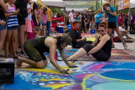 cochlear: Denver Chalk Art Fest 2014, artist blowing on Cochlear Hear Now drawing