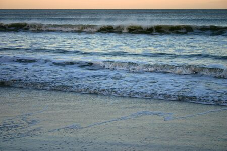 withdrawing: Beach at sunset, with several lines of surf and spray withdrawing Stock Photo