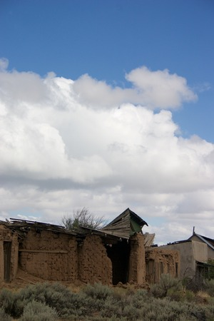 Abandoned brick and adobe buildings against the sky and clouds Stock Photo