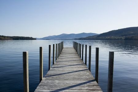 stark: Wood pier reaching out onto the lake.