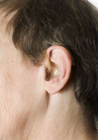 Close up of a senior woman with a hearing aid set against a white background. photo