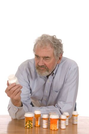 Senior man looking at prescription bottle sorting out medicine set against a white background. photo