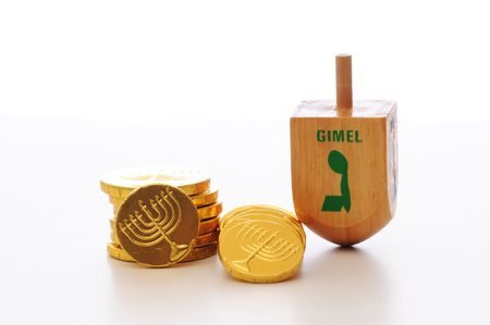 Hanukkah dreidel standing on end next to Hanukkah gelt candy set against a white background.