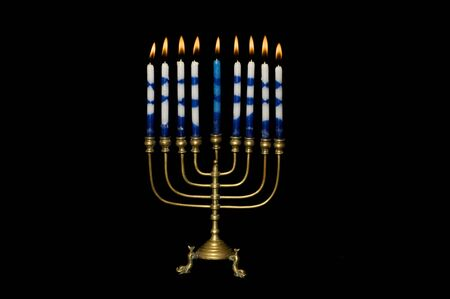 Hanukkah menorah with lighted candles set against a black background. photo