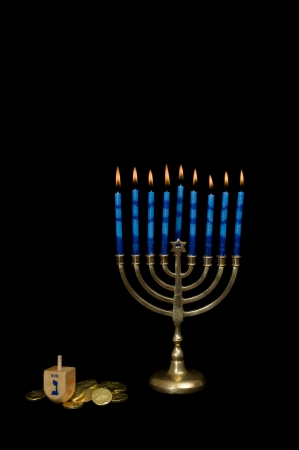 gelt: Chanukah menorah with lighted candles with gelt and a dreidel set against a black background.