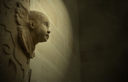 Angel is sculpted in architecture. Stylized photo of an angel. Cherubs head from the profile Stock Photo