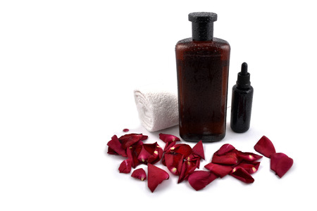 Spa still life stock images. Rose cosmetics on a white background. Rose petals with cosmetics. Cosmetic bottle photo. Vials on a white background