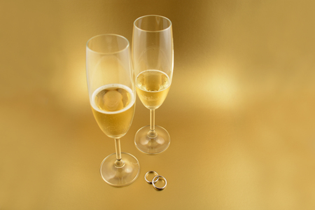 Wedding rings with champagne stock images. Golden wedding background. Valentines Day concept. Champagne on a golden background with copy space for text. Festive golden background Stock Photo