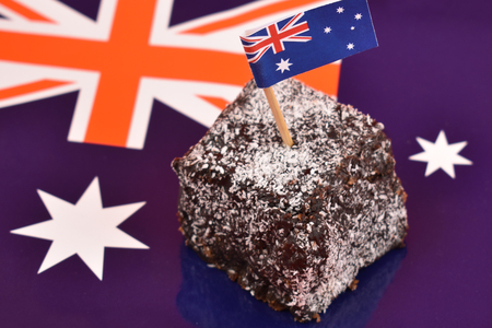 Lamington and Australian flag stock images. Lamington on a national background. Australian sweet delicacy. Important day. Lamington Day background. Australian cake with flag