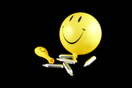 Laughing gas balloons stock images. Happy emoji balloon stock images. Smiley inflatable balloon isolated on a black background. Laughing party balloon. Laughing gas bombs stock images