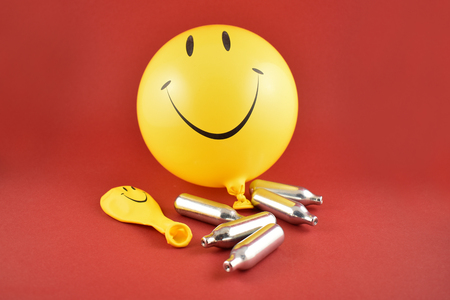 Laughing gas bombs stock images. Laughing gas balloons. Happy emoji balloon. Smiley inflatable balloon isolated on a red background. Laughing party balloon. Nitrous oxide bulbs