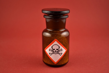 Vial with poison stock images. Vial with warning pictogram stock images. Laboratory accessories. Vials on a red background. Brown glass containers. Brown chemical glass