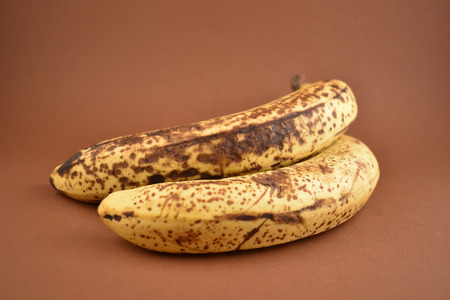 Ripe banana stock images. Brown banana on a brown background. Overripe banana images