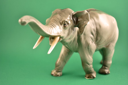 Realistic elephant statue stock images. Old porcelain statue of an elephant. Figurine elephant stock images. Elephant isolated on a green background