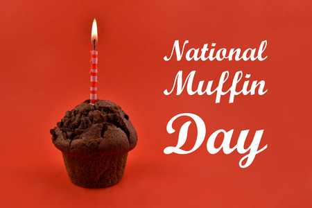 National Muffin Day images. Chocolate muffin with candle stock images. Muffins on a red background. Birthday muffin with cake candle Stock Photo