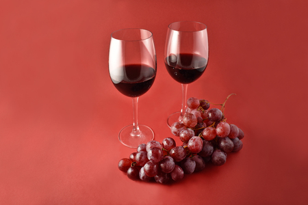 Red wine with grapes stock images. Two glasses of red wine. Red wine on red background