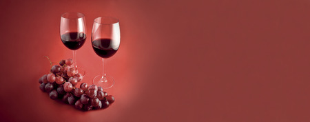 Red wine with grapes stock images. Burgundy autumn banner with wine. Two glasses of red wine. Red wine on red background