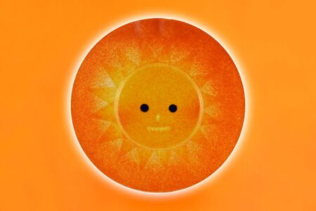 Orange sun decoration stock images. Ceramic sun isolated on a white background. Round sun ornament. Happy Sun stock images
