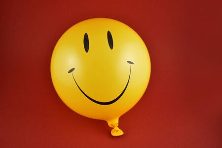 Happy emoji balloon stock images. Yellow balloon stock images. Smiley inflatable balloon isolated on a red background. Laughing party balloon