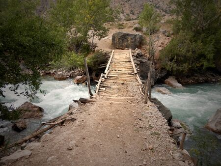 Wooden bridge in forest over wild river stock images. Tajikistan nature with river. Tajikistan Beautiful landscape images. Wild landscape in Tajikistan. Scenic view with wood bridge Zdjęcie Seryjne