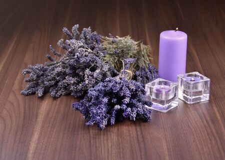 Lavender decoration stock images. Lavender on a wooden background. Bunch of french lavender. Lavender and candles images. Aromatic spa still life. Provence decoration Stok Fotoğraf